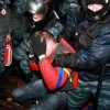Riot police officers detain a protester in Kiev