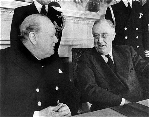 Prime Minister Winston Churchill, left, and President Franklin D. Roosevelt face each other at a conference table in the White House at Washington, Dec. 22, 1941